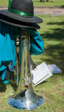 when: Brass musical instrument put on ground with hat when band takes a break on St Patricks Day Stock Photo