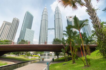 water feature: Kuala Lumpur, Malaysia- October 9, 2013: Petronas Twin Towers center in wide angle image in Kuala Lumpur flanked by architecturally modern high-rise office towers rise over footbridge and water feature