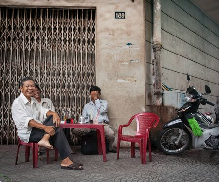 min: Saigon, Vietnam -October 12, 2013; Three Vietnamese happy smiling men sit at plastic table on plastic chairs with their drinks and cigarette packets on street corners in Vietnam, Saigon, Ho Chi Min City