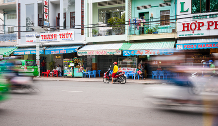 can tho: Can Tho, Vietnam - October 13, 2013: Can Tho street scene shops with shop houses above woman and children youth in red and yellow on motorcycle across street with blurred motion of passing vehicles on either side of frame.