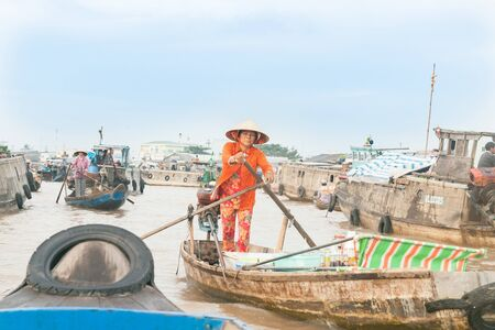 difficult lives: Can Tho Vietnam - October 14, 2013: Life and commerce on Mekong River  Can Tho Vietnam a woman in bright orange clothing rows with characteristic Vietnamese stand-up rowing method amongst boats with people living and trading.