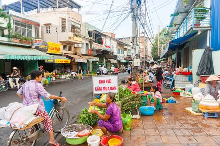 can tho: Can Tho Vietnam - October 16, 2013: Street of Vietnamese fruit and vegetable vendors camped on sidewalk in front of shops typicl shop houses on second level.