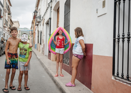 niños actuando: Xalo, Spain - August 21, 2016: Xalo street scene, Spain children playing and acting up for camera in the narrow village street in which they live and play. Editorial