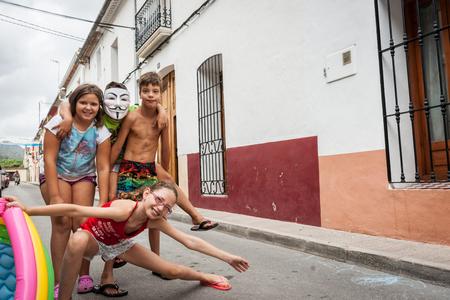 niños actuando: Xalo, España - 21 de de agosto de, 2016: escena de la calle Xaló, España niños jugando y actuando para la cámara en la estrecha calle del pueblo en el que viven y juegan.