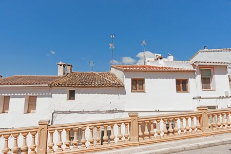 spanish village: Row of terrace stile homes with Spanish terracotta roof tiles built on sloping road in Spanish village