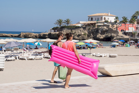 lilo: Xabia, Spain - September 7, 2016: Young couple on warm summer clear day walk anlong beautiful beach carrying  pink inflatable lilo float on Mediterranean Costa Blanca Spain