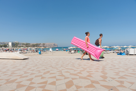 Xabia, Spain - September 7, 2016: Young couple on warm summer clear day walk anlong beautiful beach carrying  pink inflatable lilo float on Mediterranean Costa Blanca Spain