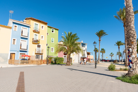 spanish homes: LA Vila Joiosa, Spain - August 25, 2016; Two peole wlk towards beach between row of pastel colored terrace style traditional Mediterranean homes with palm tree La Vila Joisa, Alicante Spain