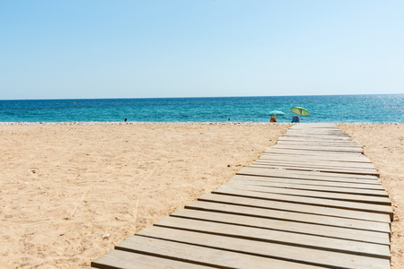 stoney: Shade umbrellas on edge of Mediterranean Sea at end walkway on white stoney beach of Alicante.