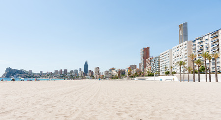 unrecognisable people: Apartment building form long view backdrop to Benidorm beach Spain unrecognisable people at seaside. Stock Photo