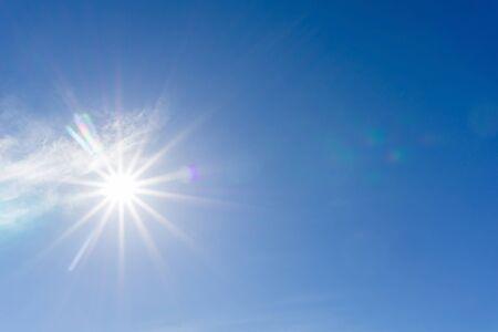 Sun erzeugt Blendenfleck gegen blauen Himmel Standard-Bild