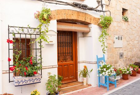 Chair and flower pots decorate home exterior in narrow Spanish traditional village streets Stock Photo