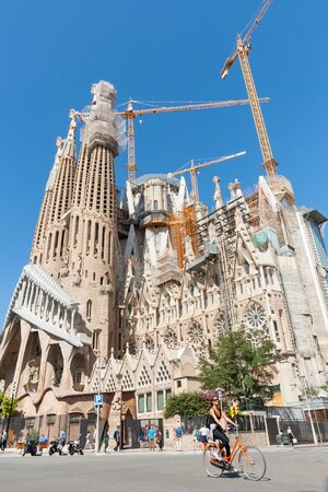 sagrada: Barcelona, Spain - September 18, 2016: Sagrada Familia, Gaudis most famous and uncompleted church cranes working while girl on bicycle passes in street below in Barcelona, Spain Editorial