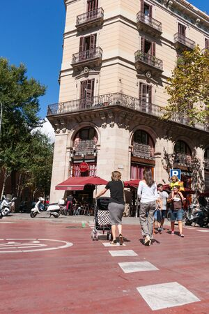 carrer: Barcelona, Spain - September 19, 2016; People cross city street  women with pushchairs walk away while young family walk other way on Carrer De LA Princesa, Barcelona, Spain Editorial