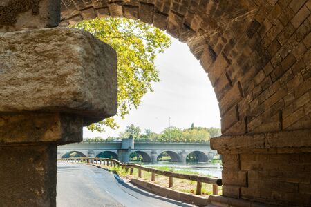 Beziers street alongside Orb River framed by stone bridge pier structure Stock Photo