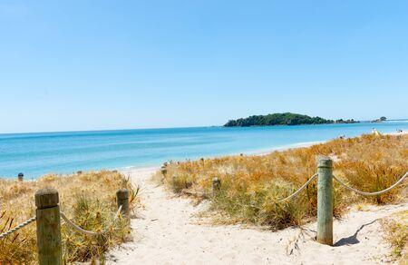 Ocean beach view beyond sand path between dunes.