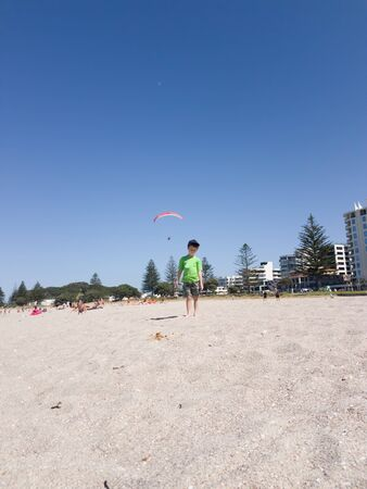 nonchalant: Boy in green tee-shirt looking nonchalantly downward on Mount Maunganui beach with paraglider landing from behind