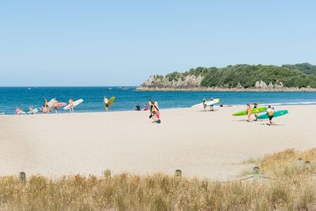 salvavidas: Tauranga, New Zealand-December 20 2016; people carrying boards and surf skis across scenic beach to sea Mount Maunganui, Tauranga, New Zealand.