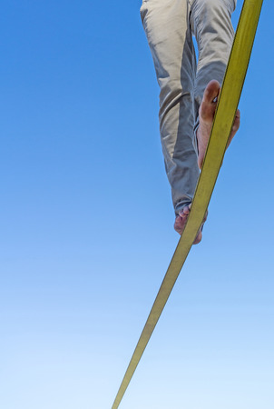 Two feet and legs on slack-line tape high in air against blue sky with balance and detrmination  reaching the end slack-line Stock Photo