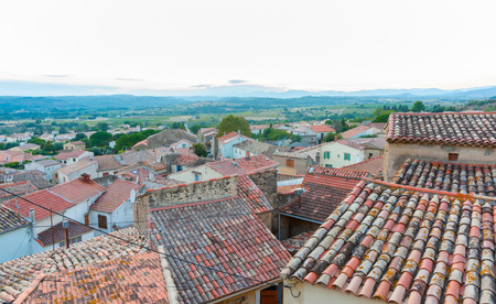 Terracotta tiled roof tops of Corneilhan sit at different angles untidily stretch into the French countryside