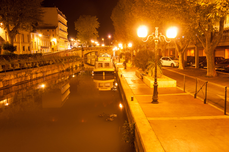 alongside: Canal boats moored alongside on Canal de la Robine at night under golden light of street lamps Narbonne, France.