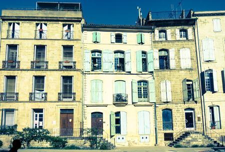 frence: Doors and windows old world effect split toned image of entrances, windows and sun bleached shutters to several traditional urban four level residential buildings in street in small Frence town Stock Photo