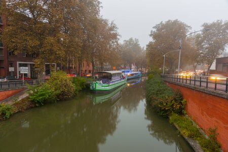 Toulouse, France -October 27, 2016; Mist shrouds long boats moored along Canal du Midi and surrounding buildings in Toulouse in south of France.