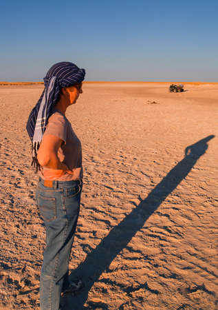 Woman stands casting long shadow as sun lowers in Makgadikgadi Pans National Park, scenic large flat area of salt pan desert of Botswana Editorial