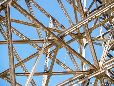 Criss-cross abstract of structural steel framing against blue sky