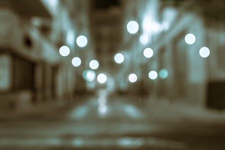 Background blue and brown tones retro effect lights in gritty urban street abstract street between buildings at night long exposure blurred defocused image.