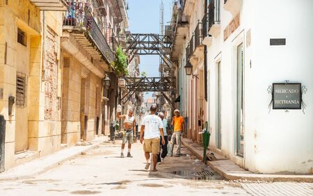 Workmaen in dilapidated buildings in street undergoing significant restoration of historic buildings as tourist walks through in Havana.