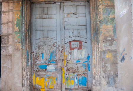 Double closed door seen best of days, daubed in paint, cracked, peeling  weathered and uncared, for in need of repairs and maintenance in Havana, Cuba Stock Photo