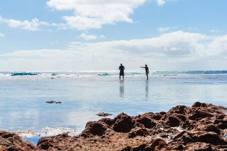 niue: Niue, South Pacific - May 25, 2017; Two figures silhouetted exploring rock pools on coral shelf on tropical Niue