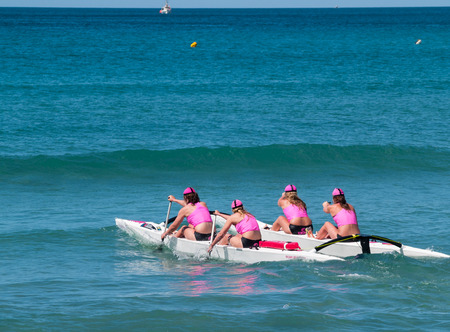 Mount Maunganui, New Zealand - January 28, 2012; Four women in pink tops returning to beach from  surf with outrigger canoe in paddling competions at Mount Maunganui, Surf Lifesaving, 2012. Four women in pink tops paddle surf outrigger canoe through surf