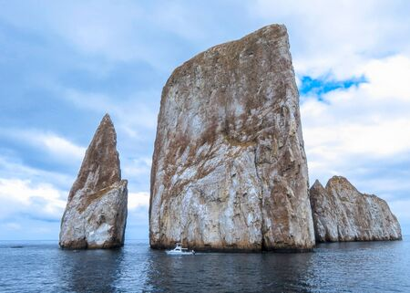 Leon Domidos or Kicker Rock, group of three rocks rising sharply from sea with small boat passing ath their base in Galapagos Islands Stock Photo