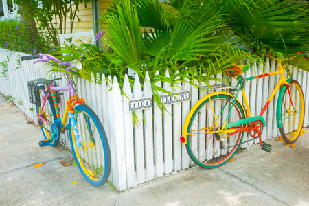 Key West, Florida, USA - June 26, 2012;  Two brightly painted bicycles leaning on picket fence on residential street corner Sajtókép