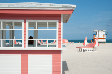 MIAMI,FLORIDA, USA - JUNE 28, 2012; Retro styled pink and white timber kiosk on beach at Miami with people seem through window.