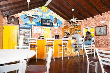 Turks and Caicos Islands, July 10, 2012;  People sitting at bar on stools and barmaid in brightly decorated Caribbean island bar. 新聞圖片