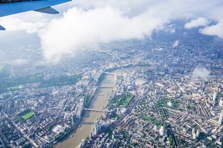 Aerial view from aircraft with wing in top left and clouds throwing shadows below,  city of London River Thames flowing through the urban and commercial capital city of United Kingdom.