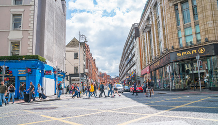 DUBLIN, IRELAND - AUGUST 10, 2017; People waiting and crossing busy city intersection with shop brands and signage on both sides