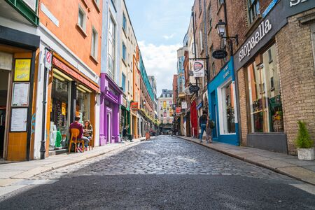 buisiness: DUBLIN, IRELAND - AUGUST 10, 2017;  Few people seated outside cafe and walking in shop and business lined narrow quaint cobbled street in Temple Bar area with shop signage on both sides Editorial