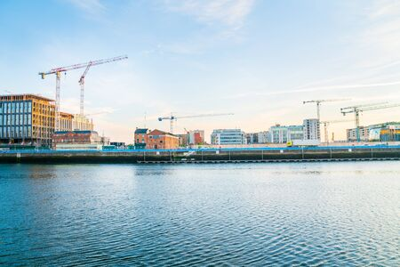 Dublin building boom illustrated in this early morning image across Liffey River an array of old wharf, modern newer, and underconstruction buildings with constructuction cranes across skyline. Ireland.