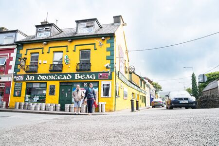 DINGLE, IRELAND - AUGUST 12, 2017; Couple wait to cross street outside small Irish pub on village street corner bright yellow and green with beer barrels on footpath outside. Editorial