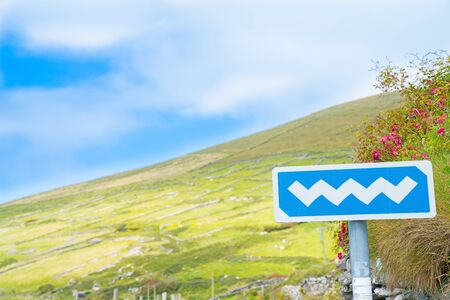 Wild Atlantic Way white on blue road sign on tourist route on Irelands west coast with landscape background. Stock Photo