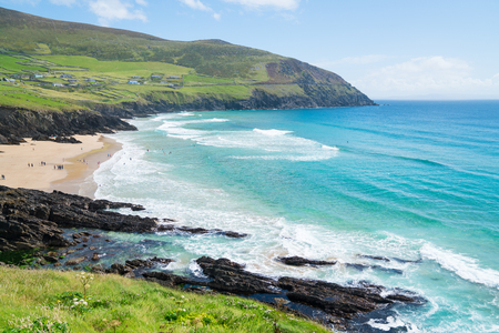 COUNTY KERRY, IRELAND- AUGUST 13, 2017; People enjoying an Irish summer day in distance on beach on west coast along Wild Atlantic Wy