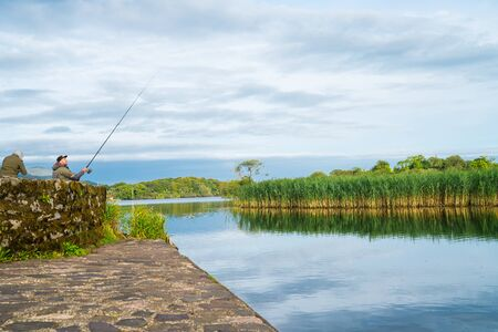 KILLARNEY, IRELAND - AUGUST 13, 2017; men out at sunrise coarse fishing from stone pier early morning on Ross Lake Ireland.