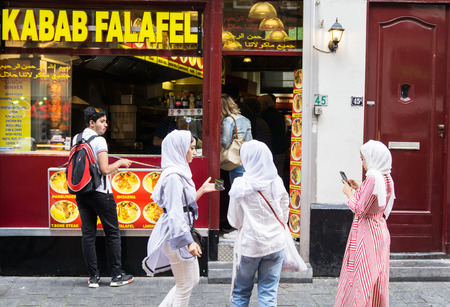AMSTERDAM, HOLLAND - AUGUST 21, 2017; Three young Muslim women in white hijab in busy city street outside Kabab Falafel Halal food shop using mobile phones from behind.