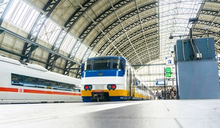 AMSTERDAM, HOLLAND - AUGUST 21, 2017; Centraal station roof architecture and people on platform waiting for their train