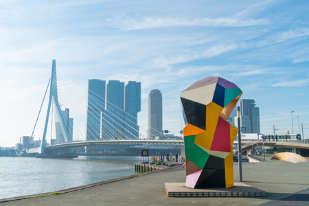 ROTTERDAM, HOLLAND -AUGUST 22, 2017; Multi-colored cubic sculpture Marathon Image in Erasmuburg district with citys stunning modern architectural buildings forming backdrop