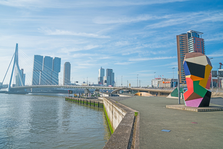 ROTTERDAM, HOLLAND -AUGUST 22, 2017; Multi-colored cubic sculpture Marathon Image on waterfront in Erasmuburg district with citys stunning modern architectural buildings forming backdrop